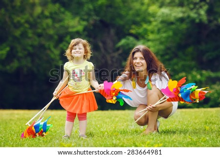 Portrait of a cute adorable toddler girl and her mother, sister, white Caucasian females, holding windmill pinwheel toy standing outside in field meadow on green grass, summer fun concept - stock photo