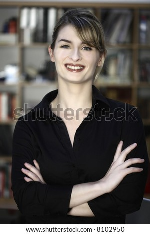portrait of a cute and smiling businesswoman at the office desk - stock photo