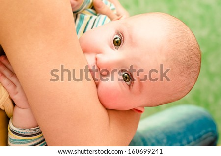 Portrait of a cute baby biting her mother's arm - stock photo