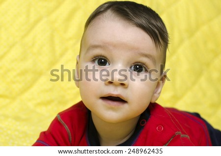 Portrait of a cute baby boy. Baby looking up curious and surprised. - stock photo