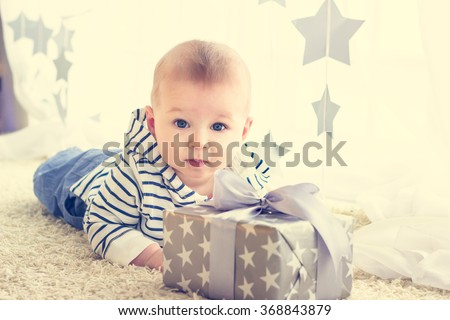 Portrait of a cute baby boy with big blue eyes wearing jeans and striped hoodie sweater lying in front of his present in wrapped box with ribbon. Birthday, Mother's day or Christmas presents concept - stock photo