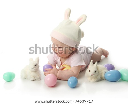 Portrait of a cute baby dressed in Easter bunny ears with eggs - stock photo