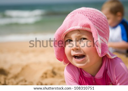 Portrait of a cute baby girl in a hat at the beach - stock photo
