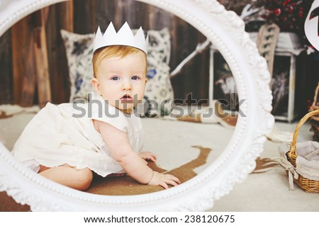 Portrait of a cute baby girl in white dress with a paper crown in the frame - stock photo