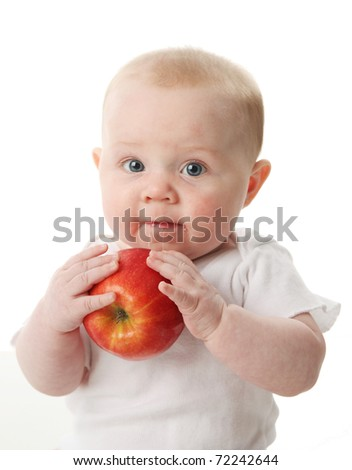 Portrait of a cute baby holding and tasting an apple