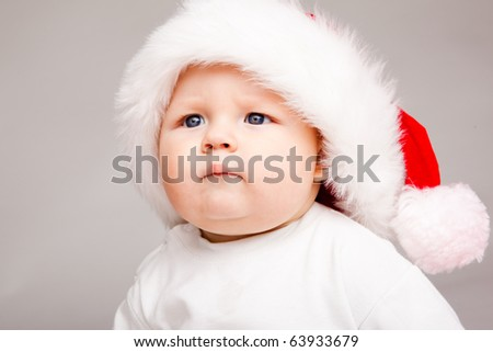 Portrait of a cute baby in a Santa hat, over gray - stock photo