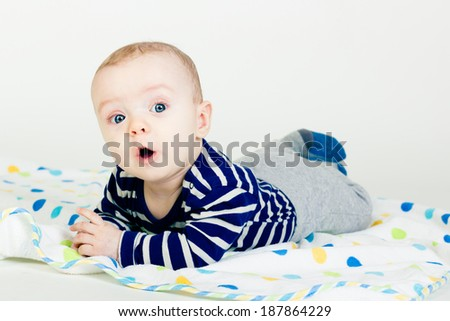 Portrait of a cute baby in striped clothes lying down on a blanket - stock photo