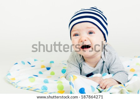 Portrait of a cute baby in striped hat lying down on a blanket - stock photo