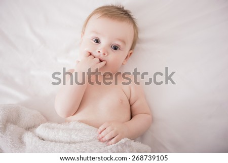 Portrait of a cute baby on the bed in her room.