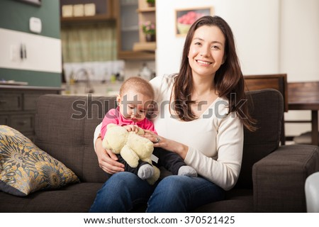 Portrait of a cute babysitter taking care of a baby girl at home - stock photo