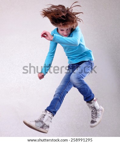 Portrait of a cute barefoot sportive, cheerful happy girl with her hands up jumping and dancing. Childhood, freedom, happiness concept. - stock photo