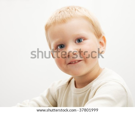 Portrait of a cute blond boy photographed on light background