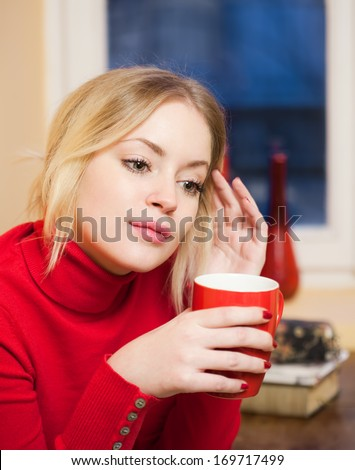 Portrait of a cute blond girl with a cup of hot beverage.