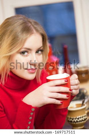 Portrait of a cute blond girl with a cup of hot beverage. - stock photo