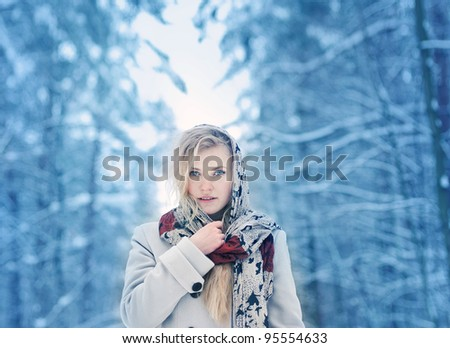 Portrait of a cute blonde in the winter forest - stock photo