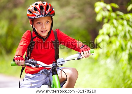 Portrait of a cute boy on bicycle - stock photo
