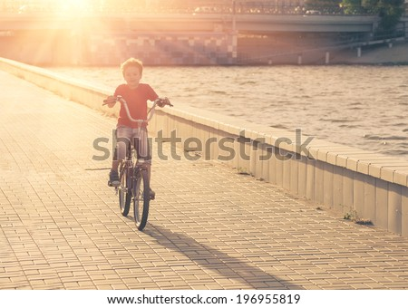 Portrait of a cute boy on bicycle. Young school boy  on a bicycle backlit against sunlight