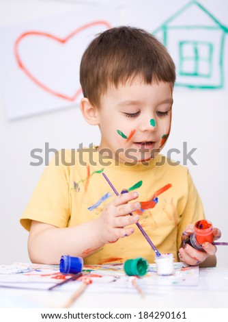 Portrait of a cute boy showing her hands painted in bright colors - stock photo