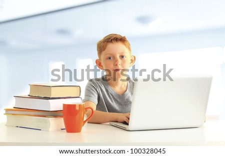 Portrait of a cute boy sitting in the school and learning on his laptop computer - stock photo