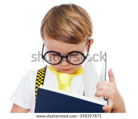 Portrait of a cute boy with glasses reading a book