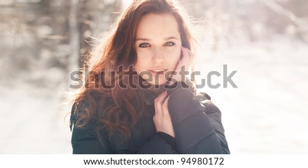 Portrait of a cute brunette in a frosty park. Photos in warm colors - stock photo