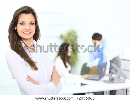 Portrait of a cute business woman with colleagues at the background - stock photo