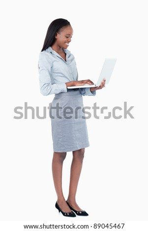 Portrait of a cute businesswoman using a laptop while standing up against a white background - stock photo