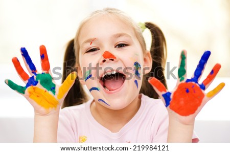 Portrait of a cute cheerful girl showing her painted hands - stock photo