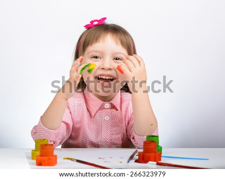 Portrait of a cute cheerful happy little girl showing her hands painted in bright color - stock photo