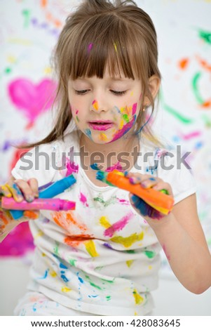 Portrait of a cute cheerful happy little girl showing her hands painted in bright colors