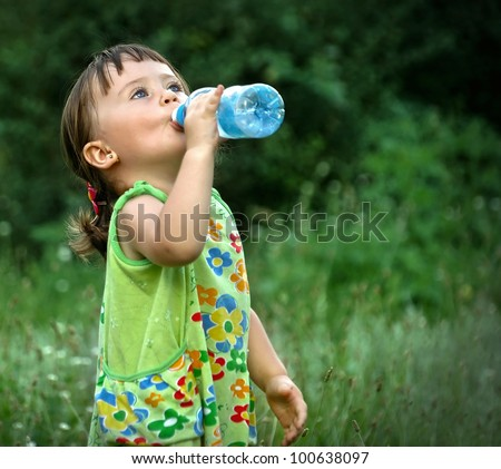 Portrait of a cute child drinking water from a bottle in the forest