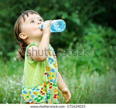Portrait of a cute child drinking water from a bottle in the forest - stock photo