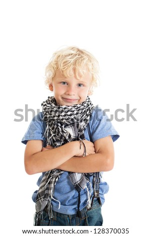 Portrait of a cute curly blond boy wearing a blue T-shirt, jeans and Arabic scarf. Studio shot, isolated on white background. - stock photo
