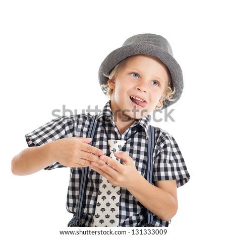 Portrait of a cute curly blond European boy wearing a plaid shirt, tie and hat. The boy explains something. Studio shot, isolated on white background. - stock photo