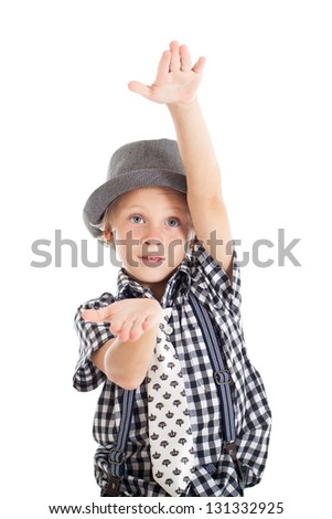 Portrait of a cute curly blond European boy wearing a plaid shirt, tie and hat. The boy showing something with his hands. Studio shot, isolated on white background. - stock photo