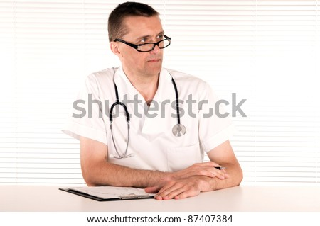 portrait of a cute doctor at table on white