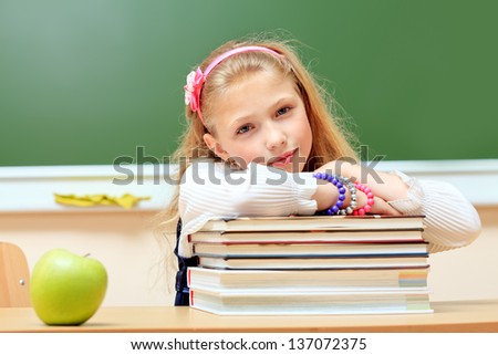Portrait of a cute dreaming schoolgirl in a classroom. - stock photo