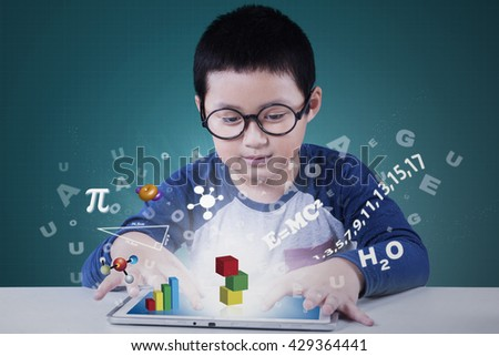 Portrait of a cute elementary school student using application on the tablet for studying - stock photo