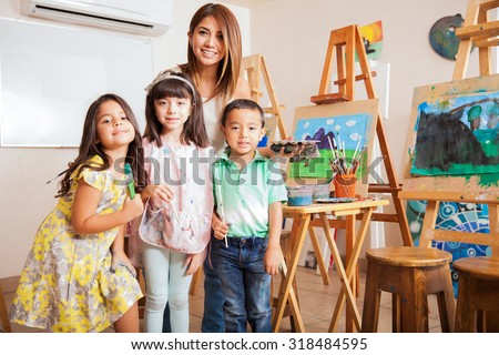 Portrait of a cute female art class teacher standing with some of her favorite students - stock photo