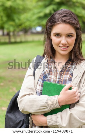 Portrait of a cute first-year student holding a textbook while posing in a park - stock photo