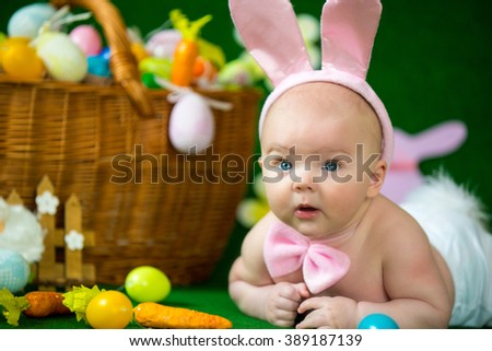 Portrait of a cute funny baby dressed in Easter bunny ears with eggs