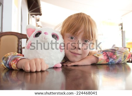 Portrait of a cute girl at the table - stock photo