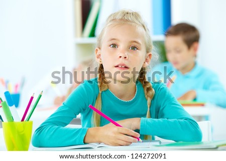 Portrait of a cute girl doing tasks at school - stock photo