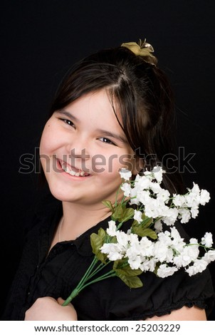 Portrait of a cute girl holding some white flowers, shot against a dark background - stock photo
