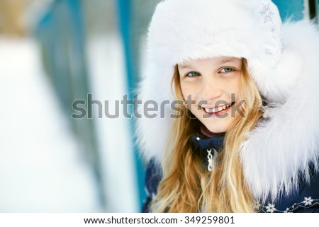 portrait of a cute girl on a walk in the winter. teen outdoors - stock photo