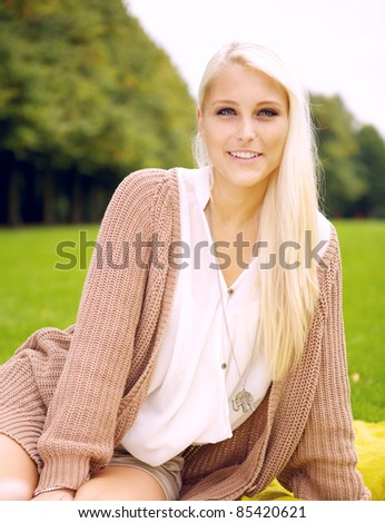 Portrait of a cute girl sitting on a blanket in a park - stock photo
