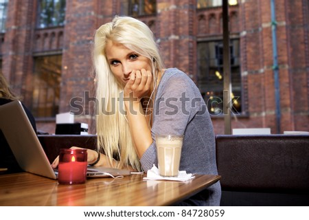 Portrait of a cute girl sitting on a cafe. - stock photo