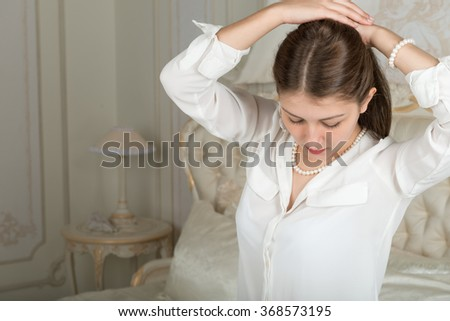 Portrait of a cute girl with beautiful long straight hair in a white blouse on the bed
