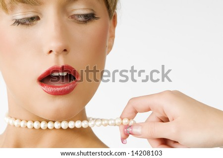portrait of a cute girl with red lips and pearls necklace pulling by one hand - stock photo