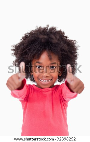 Portrait of a cute girl with the thumbs up against a white background - stock photo